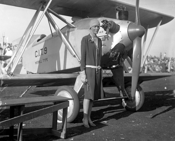 Black and white photo of Amelia next to plane.